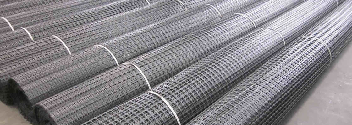 Many rolls of biaxial geogrids tied with white plastic belts.