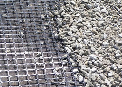 A piece of biaxial geogrid under gravel.