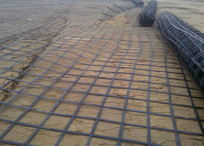 Many rolls of steel plastic geogrids are spreading on the ground.