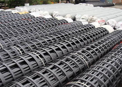 Many rolls of steel plastic geogrids on the ground.